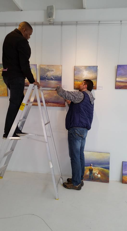 Patso Nikolov and Edward busy rearranging the paintings of Hester Hattingh